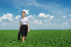 Girl with a briefcase walking on grass Stock Images