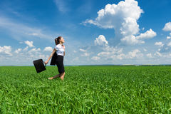 Girl with briefcase walking on the grass Royalty Free Stock Photography
