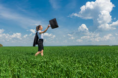 Girl with a briefcase walking on the grass Stock Images