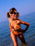 A girl in a bright bathing suit and dark glasses a. Female teenager poses. The hair gathered in a ponytail. Bright swimsuit. Sunglasses. She looks into the Royalty Free Stock Photos