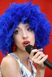 Girl in  bright, blue wig, sings. Stock Photos