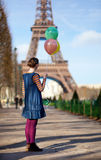 Girl in bright clothes with colorful balloons Stock Image