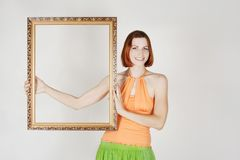 Girl in bright clothes holding decorative frame Stock Photos