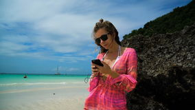 Girl in bright clothes listening to music on a white beach in stone. Young woman putting headphones in ear by sea shore. stock footage