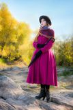Girl in a bright crimson coat looks into the distance Stock Photo