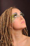 Girl with bright exotic makeup. Braids and sequins Stock Images