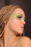 Girl with bright exotic makeup. Braids and sequins Stock Image