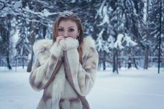Girl in a bright fur coat with flowing hair and snow on her hair put her hands to her face against the background of the winter stock image