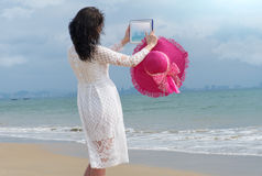Girl with bright hat and iPad makes the photo. The girl with bright hat and iPad looks to the sea and makes the photo Stock Image