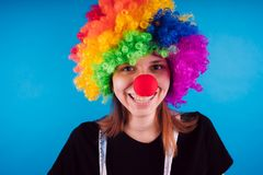 Girl in a bright image of a clown. emotional portrait of a student. costumed presentation of children`s animator. stock photos