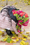 The girl in a bright kerchief cleans foliage Stock Photo