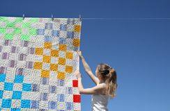 Girl and bright laundry. Girl touching a bright patchwork counterpane hanging to dry on a clothes-line stock photo