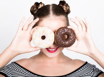 Girl in bright makeup eating a tasty donut with icing. Funny joyful woman with sweets, dessert. dieting concept. junk Stock Photo