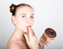 Girl in bright makeup eating a tasty donut with icing. Funny joyful woman with sweets, dessert. dieting concept. junk Royalty Free Stock Photography
