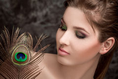 Girl with bright  makeup and peacock feathe Stock Photos