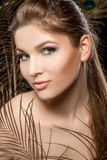 Girl with bright  makeup and peacock feathe Royalty Free Stock Image