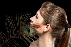 Girl with bright  makeup and peacock feathe Royalty Free Stock Images
