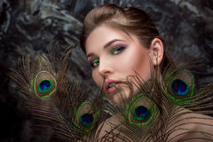 Girl with bright  makeup and peacock feathe Royalty Free Stock Photography