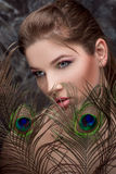 Girl with bright  makeup and peacock feathe Stock Images