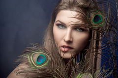 Girl with bright  makeup and peacock feathe Royalty Free Stock Photos