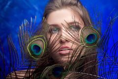 Girl with bright  makeup and peacock feathe Royalty Free Stock Photo