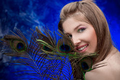 Girl with bright  makeup and peacock feathe Stock Photography