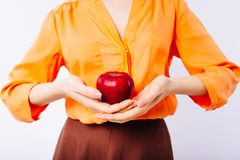 Girl in a bright orange sweater with an apple in her hands promotes healthy food. stock images