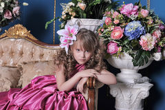 Girl in a bright pink dress. Sitting on couch Royalty Free Stock Photos