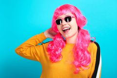 Girl with bright pink hair in sunglasses. Beautiful smiling caucasian girl with bright pink hair in sunglasses on blue background stock photo