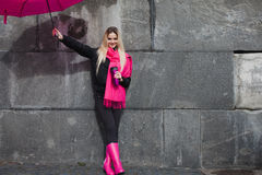 Girl in a bright pink scarf, rubber boots and umbrella on the background of gray stone wall Stock Image