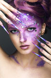 Girl with bright purple creative makeup with crystals and long nails. Beauty face. Stock Images