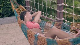 Girl in bright red bikini with long legs rests in hammock stock video