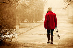 Girl in a bright red coat walking in the park with a dog on a cl. Oudy autumn day. Sepia Royalty Free Stock Image