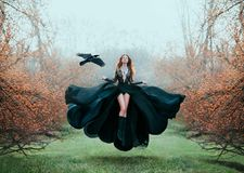 Girl with bright red hair levitates above ground, powerful sorceress, forest goddess in black flying dress with lace on
