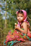 A girl in a bright sarafan sitting on a stump Royalty Free Stock Images