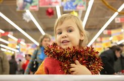 Girl with bright tinsel in store stock photos