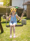 A girl with bright yellow flowers on his head swinging on an old swing in the village. Beautiful girl in the rays of the sun with the decoration of flowers on Royalty Free Stock Photography