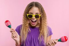 Girl In bright yellow glasses she dances with maracas on a pink background stock photography