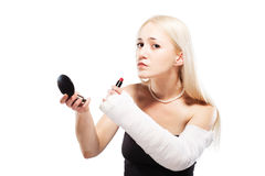 Girl with a broken arm trying to put makeup. Blond girl with a broken arm in plaster having trouble putting a lipstick stock photography