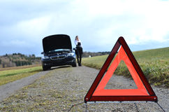 Girl, broken car and triangle Royalty Free Stock Photo