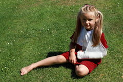 Girl with broken hand. Barefoot girl in red dress with broken hand sitting on the grass royalty free stock photography