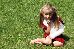 Girl with broken hand. Barefoot girl in red dress with broken hand sitting on the grass stock photo