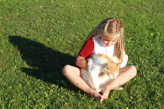 Girl with broken hand and cat. Barefoot girl in red dress with broken hand sitting on the grass with a cat stock images