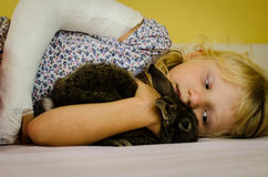 Girl with broken hand and rabbit Stock Photos