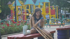 Girl with a broken leg sits on a bench, on the background of a descriptive pad and looks at the smartphone. Little girl with crutches at the stair. Back to stock footage