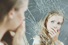 Girl and broken mirror. Girl with mental problem looking at herself in a mirror Stock Photo
