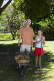 Girl (10-12) with broom by father with wheelbarrow outdoors, portrait Royalty Free Stock Photos
