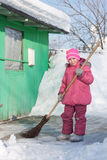 Girl with a broom. A girl with a broom outside royalty free stock photo