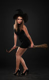 The girl with the broom is standing. In the studio Stock Image