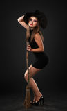The girl with the broom in the studio. The girl with the broom in the dark studio Royalty Free Stock Photography